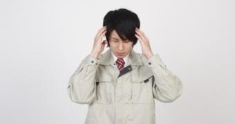頭痛の作業服の男性